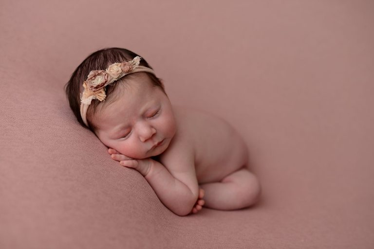 Newborn baby girl on pink background in Queens Portrait Studio